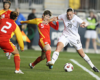 Abby Wambach #20 of the USA WNT holds off Xinzhi Weng #5 of the PRC WNT during an international friendly match at PPL Park, on October 6 2010 in Chester, PA. The game ended in a 1-1 tie.