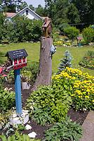 Bird feeders, ornaments, circular beds, colorful flowers, lawn grass, wheelbarrow planter, cute backyard garden