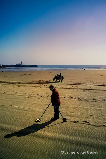Traditional and modern recreational seaside activities as beachcombing with a metal detector and a children's donkey ride coincide on Scarborough's South Bay beach in chilly early April sunshine.