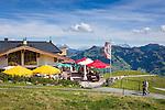 Austria, Tyrol, above Kitzbuehel: restaurant 'Hahnenkamm Stueberl', at background Loferer Steinberge mountains (left) and Leoganger Steinberge mountains (right) | Oesterreich, Tirol, oberhalb Kitzbuehel: Restaurant Hahnenkamm Stueberl, im Hintergrund die Loferer Steinberge (links) und die Leoganger Steinberge (rechts)