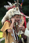A young Native American Indian boy plugging his ears from a loud noise from a antler bone whistle