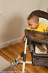 10 month old baby boy in high chair leaning over to drop toy