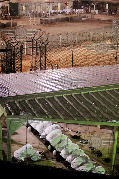 Guantanamo detainees pray before dawn near a razor-wire fence inside Camp Delta at the American naval base at Guantanamo Bay, where over 600 alleged al Qaeda members have been held indefinitely. Described by the US as 'unlawful enemy combatants', they were captured primarily in Afghanistan during the 'war against terror'.