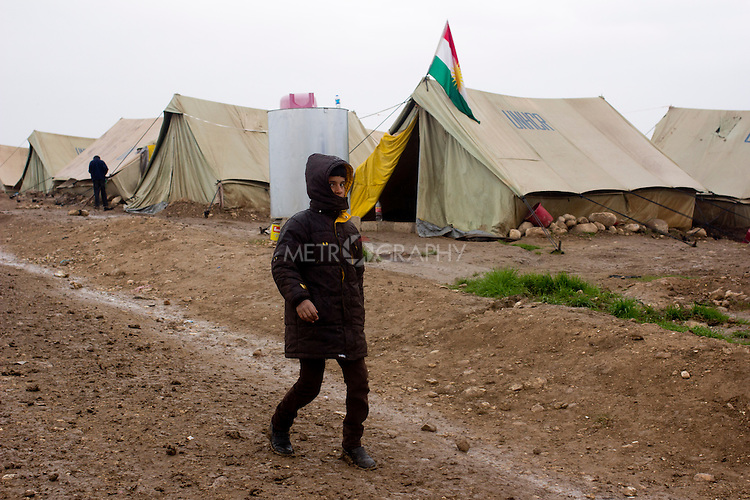 DOMIZ, IRAQ: A young Syrian refugee walks through the Domiz refugee camp in the Kurdish region of northern Iraq...The semi-autonomous region of Iraqi Kurdistan has accepted around 60,000 refugees from war-torn Syria. Around 20,000 refugees live in the Domiz camp which sits 60 km from the Iraq-Syria border...Photo by Younes Mohammad/Metrography