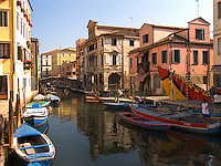 Fishing boats and houses along Vena canal in Chioggia Italy