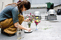 A young woman prepares discarded flowers for a centerpiece before a community meal in New York City on April 7, 2006.