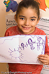 Education preschool 4-5 year olds art activity proud girl holding up picture she drew recognizable human figure vertical