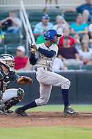 Raimel Tapia (15) of the Asheville Tourists follows through on his swing against the Kannapolis Intimidators at CMC-NorthEast Stadium on July 12, 2014 in Kannapolis, North Carolina.  The Tourists defeated the Intimidators 7-5 in 15 innings.  (Brian Westerholt/Four Seam Images)