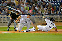Jacksonville Suns third baseman Zack Cox #40 tags out Ryan LaMarre #23 as umpire Bradley Lawhead gets ready to make the call during a game against the Pensacola Blue Wahoos on April 15, 2013 at Pensacola Bayfront Stadium in Pensacola, Florida.  Jacksonville defeated Pensacola 1-0 in 11 innings.  (Mike Janes/Four Seam Images)