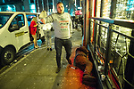 """© Joel Goodman - 07973 332324 . 15/12/2017. Manchester, UK. A man , believed to be homeless , sleeps on the pavement in front of a club on Peter Street , as revellers walk around him . Revellers out in Manchester City Centre overnight during """" Mad Friday """" , named for historically being one of the busiest nights of the year for the emergency services in the UK . Photo credit : Joel Goodman"""