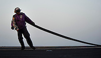110418-N-DR144-456 ARABIAN SEA (April 18, 2011) Aviation Boatswain's Mate (Fuel) Airman Kevin Daniels, assigned to Air Department's V-4 Division, drags a fuel hose to an aircraft on the flight deck of Nimitz-class aircraft carrier USS Carl Vinson (CVN 70).  Carl Vinson and Carrier Air Wing (CVW) 17 are conducting maritime security operations and close-air support missions in the U.S. 5th Fleet area of responsibility. (U.S. Navy photo by Mass Communication Specialist 2nd Class James R. Evans / Released)