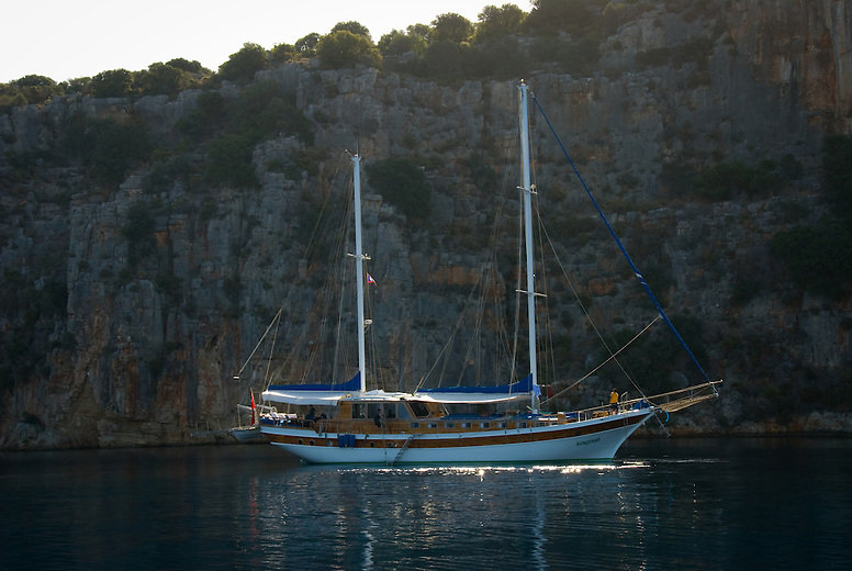 A Turkish gulet on the Mediterranean Sea. These broad-beamed wooden coastal sailing vessels were first used to transport cargo on ancient Mediterranean trade routes. Today gulets are beautiful floating villas for tourists and vacationing locals, mostly motoring along the shoreline.