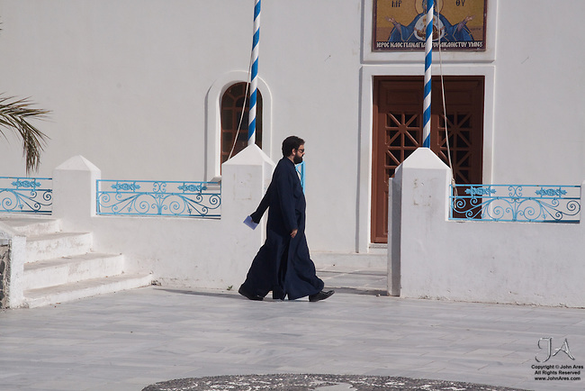 Priest walking in Oia Square