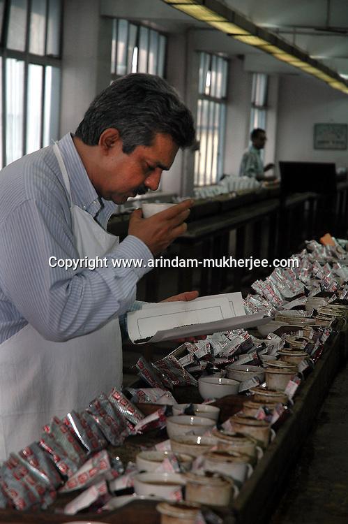 A tea tester smells a cup of tea at the tea testing room of  J. Thomas ltd. company in Kolkata, West Bengal,  India, Arindam Mukherjee