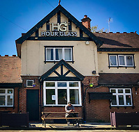 A lone person sits outside the Hour Glass pub in the sun during the COVID-19 pandemic lockdown as the UK Government advice to maintain social distancing and minimise time outside in High Wycombe on 20 April 2020. Photo by PRiME Media Images / Andy Rowland.
