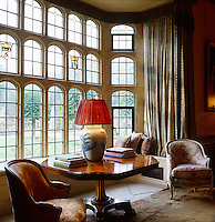 A polished hexagonal table, flanked by a pair of armchairs, stands in a mullioned bay window in the hall