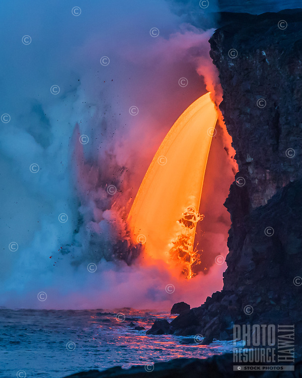 """Lava Fall: A fire hose of lava or """"lava fall"""" at the Kamokuna ocean entry for Kilauea Volcano, Big Island. This is by far the most volume and fastest amount of lava a fire hose (or lava hose) has produced in recorded history. Photo taken at the """"Blue Hour"""" (transition of dawn light into daylight), January 29, 2017."""