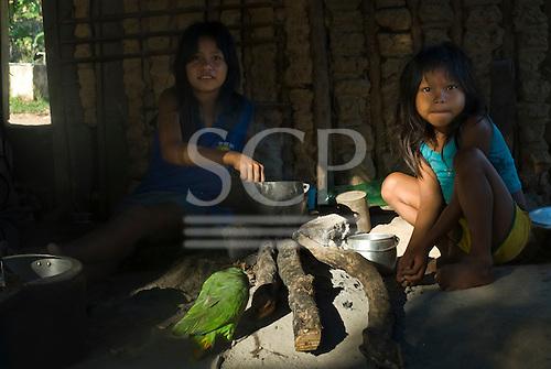 Pará State, Brazil. Iriri River. Aldeia Kararaô (Kayapó). Woman, girl and pet parrot.