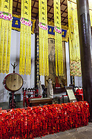 Nanjing, Jiangsu, China.  Portrait of Confucius in the Dacheng Temple Building of the Confucian Temple Complex.  Red tassles are prayers for good luck.
