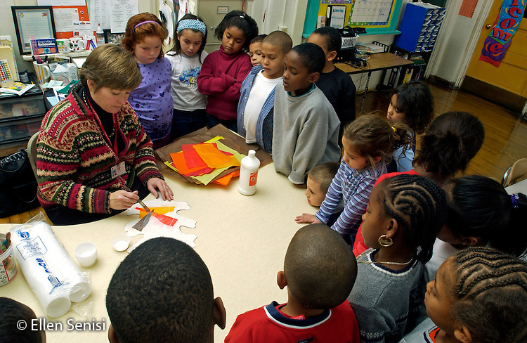 MR / Schenectady, NY.Yates Arts in Education Magnet School, Grade 2.Arts-Themed Urban Elementary School.Teacher gives directions to students for doing in-class art project on fall colors using tissue paper and glue..MR: g2c.© Ellen B. Senisi