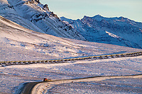 Trucker travels the Dalton highway as it winds out of Atigun canyon, the Trans Alaska oil pipeline adjacent to the raod.