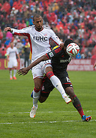 Toronto, Ontario - May 3, 2014: Toronto FC defender Doneil Henry #15 battles for a ball with New England Revolution forward Teal Bunbury #10 during a game between the New England Revolution and Toronto FC at BMO Field.<br /> The New England Revolution won 2-1.
