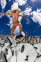 A sexy girl tears it up on a skateboard.