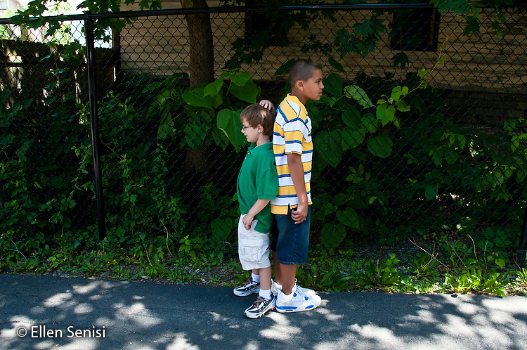 MR / Schenectady, New York. Elmer Avenue School (urban public elementary school). Two students (boys, age 9) stand back to back to measure their difference in height. They are the same age but show maturational differences in body development. MR: Sze6, Kel2. ID: AK-g3m. ©Ellen B. Senisi