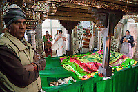 Fatehpur Sikri, Uttar Pradesh, India.  Inside the Mausoleum of Sheikh Salim Chishti.  Women Pray at the Tomb in the Hope of Conceiving a Child.  Caretaker on Left, Monetary Offerings in front.