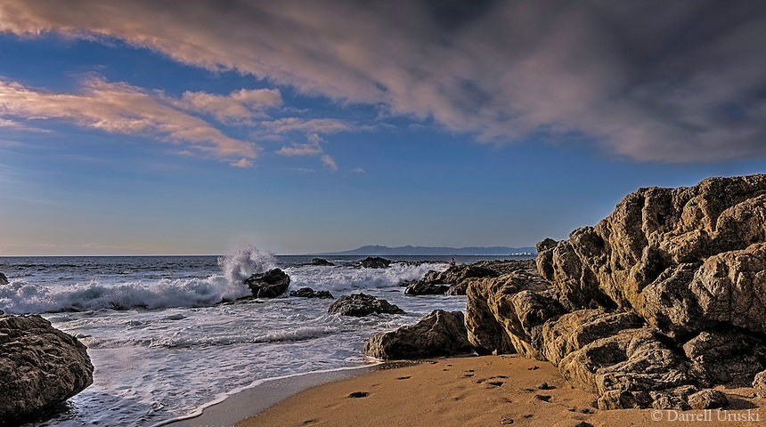 Fine Art Photograph of a secluded beach in Puerto Vallarta, Mexico. A solitary person sitting on the rocks watches as the waves from the ocean crash on the rocks, and then flows onto the sandy beach.
