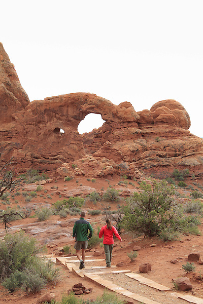 Couple walking to Turret Arch in the Windows Section, Arches National Park, Moab, Utah, USA. .  John offers private photo tours in Arches National Park and throughout Utah and Colorado. Year-round.