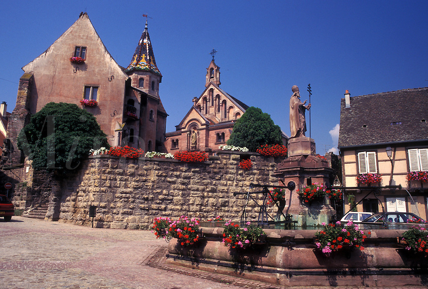 France, Alsace, Eguisheim, Haut-Rhin, Europe, wine region, Cathedral and fountain decorated with flowers in the picturesque village of Equisheim in the wine region of Alsace.