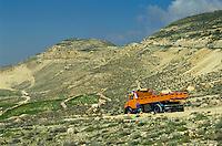 Truck driving through the dirt road of a desert, Jordan.