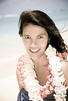 Tourist arriving to Hawaii with plumeria flower leis at a sunny beach with blue water