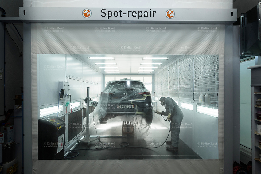 """Switzerland. Canton Geneva. Plan-les-Ouates. Renault Retail Group, RRG Suisse. """"Spot-repair"""" by Dells Angels. Renault Clio car inside a paint booth in auto body repair garage. After filling bumpy part and grinding automobile car body in garage workshop, the mechanic worker is painting the repaired spot. 4.03.2020 © 2020 Didier Ruef"""
