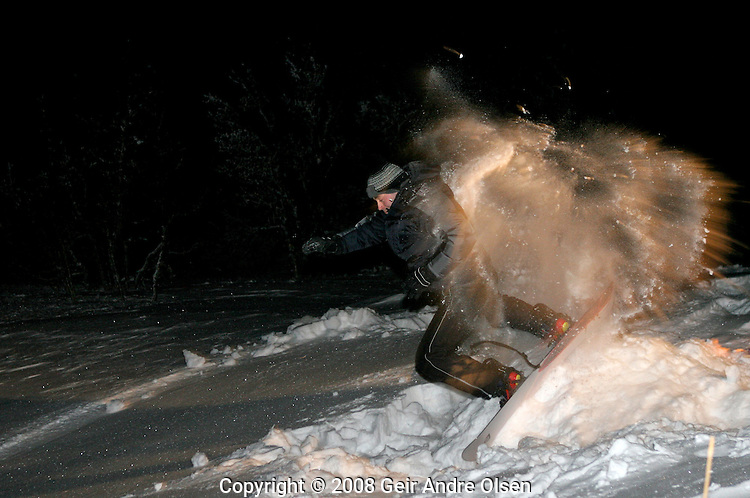 Man jumping on snowboard with lots of snow around him