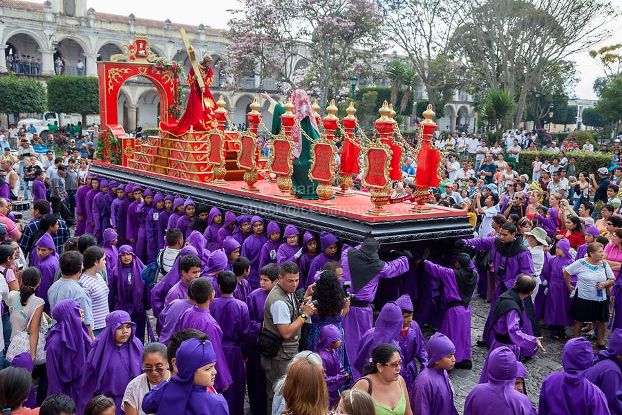 Antigua, Guatemala.  Young Cucuruchos Carry an Anda Past the Plaza de Armas, Semana Santa.