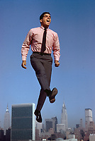 Experimental photo for Grey Advertising, Van Heusen Shirt Ad (unpublished). Model jumps on trampoline on roof of Pepsi building, New York skyline behind, 1963. Photo by John G. Zimmerman.