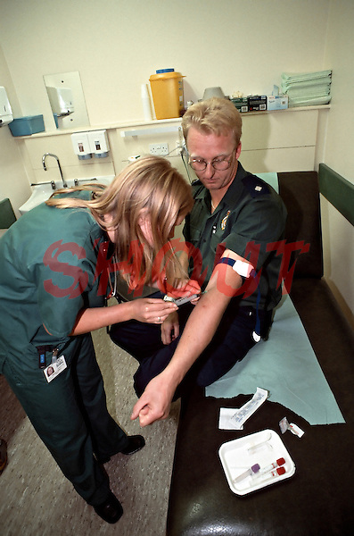 Doctor taking a blood sample for analysis from a paramedic prior to injecting him with an intramuscular tetanus injection as part of a course of treatment after he was cut whilst dealing with a HIV infected casualty. The paramedic was rushed into the crash room of an accident and emergency department.