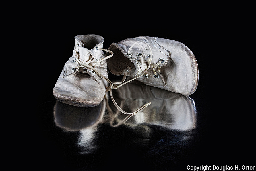 Baby Shoes, leather, circa 1950, vintage baby shoes on black reflective background.