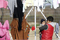 Pictured: A boy holds his younger brother by a fence Thursday 25 February 2016<br /> Re: Refugees have been left stranded in temporary camps after Greek FYRO Macedonian borders were closed in Idomeni, northern Greece.