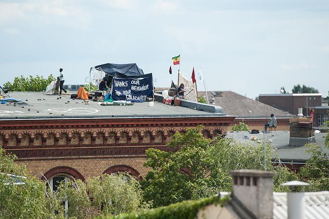 """Fluechtlingsprotest auf dem Dach der Gerhard-Hauptmann-Schule in der Ohlauer Strasse in Berlin-Kreuzberg.<br /> Seit dem 24. Juni 2014 haben harren Fluechtlinge und deren Unterstuetzer auf dem Dach der Gerhard-Hauptmann-Schule aus. Sie hatten sich geweigert dem sog. """"Freiwilligen Umzug"""" zu folgen, der vom Gruenen Bezirksstadtrat Hans Panhoff angeordnet worden war. Die Polizei war bei der als """"Umzug"""" geschoenten Raeumung mit gezogenen Maschinenpistolen angerueckt.<br /> Baustadtrat Panhoff hat am 1. Juli 2014 die polizeiliche Raeumung des Schulgebaeudes beantragt. Einige der Fluechtlinge haben angekuendigt, im Fall der Raeumung vom Dach zu springen. """"Wir haben nichts mehr zu verlieren!"""" sagen sie.<br /> Die Polizei hat seit dem 24. Juni mit ueber 1.000 Beamten saemtliche Strassen um die Schule abgeriegelt. Anwohner duerfen nur nach Personalienfeststellung in ihre Wohnungen, Geschaefte und Gewerbe koennen keine Kundschaft mehr empfangen. Anwohner die gegen das Vorgehen der Polizei protestieren werden von Beamten drangsaliert, geschlagen und verletzt. Mehrere Personen, darunter auch Kinder mussten zum Teil mit Kieferbruch ins Krankenhaus.<br /> 2.7.2014, Berlin<br /> Copyright: Christian-Ditsch.de<br /> [Inhaltsveraendernde Manipulation des Fotos nur nach ausdruecklicher Genehmigung des Fotografen. Vereinbarungen ueber Abtretung von Persoenlichkeitsrechten/Model Release der abgebildeten Person/Personen liegen nicht vor. NO MODEL RELEASE! Don't publish without copyright Christian-Ditsch.de, Veroeffentlichung nur mit Fotografennennung, sowie gegen Honorar, MwSt. und Beleg. Konto: I N G - D i B a, IBAN DE58500105175400192269, BIC INGDDEFFXXX, Kontakt: post@christian-ditsch.de<br /> Urhebervermerk wird gemaess Paragraph 13 UHG verlangt.]"""
