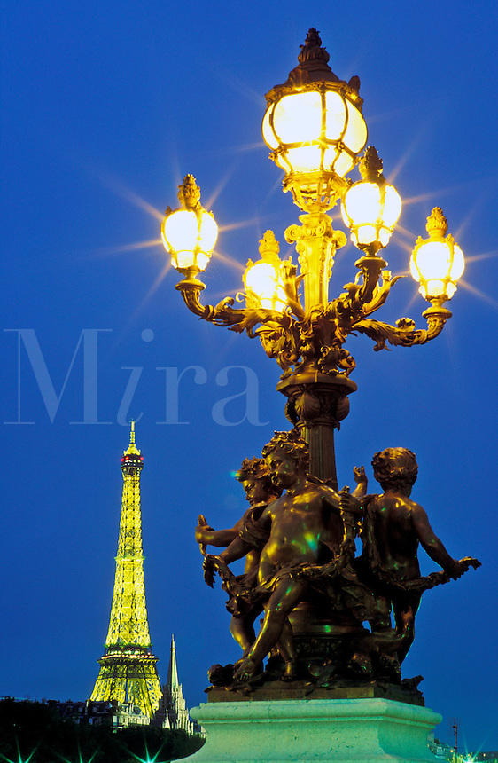 France, Paris. Lamp post on Pont Alexandre III and Eiffel Tower illuminated at night