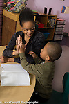 """Education Preschool 3-4 year olds female teacher gives boy a """"high five"""" for signing in in the morning"""