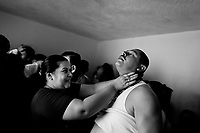 A Colombian believer, pressing on a fellow believer's neck, attempts to evict a supposed demon during the exorcism ritual performed at a house church in Bogota, Colombia, 28 January 2013. Hundreds of Christian belivers, joined in nameless groups, gather every week in unmarked home churches dispersed in the city outskirts, to carry out prayers of liberation and exorcism. Community members and their religious activities are usually conducted by a charismatic pastor or preacher. Using either non-contactive methods (reading religous formulas from bible, displaying Christian symbols and icons) or rough body-pressure-points techniques and forced burping, a leading pastor commands the supposed evil spirit, which is generally believed to come from witchcraft, to depart a person's mind and body. The demon's expulsion often consists of multiple rites and may last for several months.