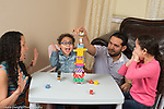 3 year old boy at home stacking game with sister age 8 and parents