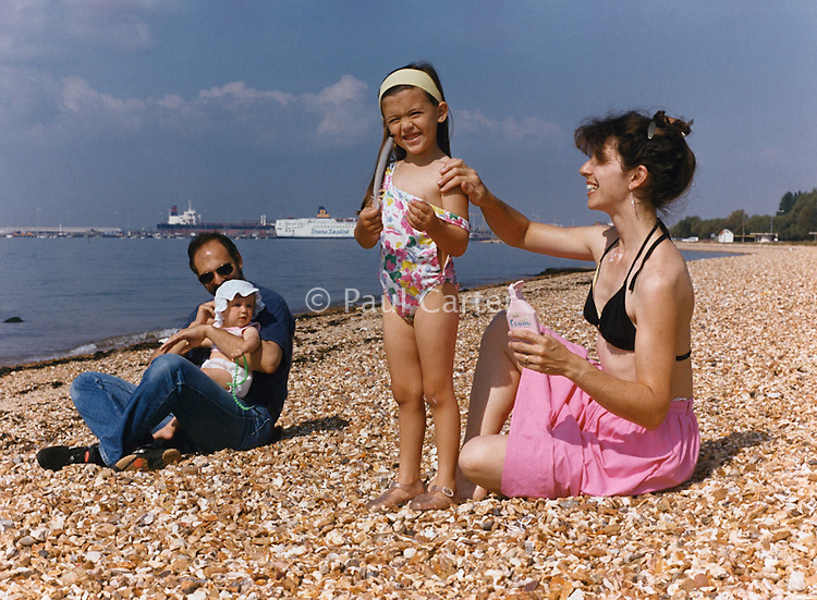 Mother applying sunscreen to her young daughter's shoulder with father holding the baby in the background.
