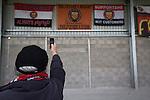 FC United of Manchester 0 Benfica 1, 29/05/2015. Broadhurst Park, Stadium Opening. A fan taking a picture of flags inside Broadhurst Park, Manchester, the new home of FC United of Manchester before the club's match against Benfica, champions of Portugal, which marked the official opening of their new stadium. FC United Manchester were formed in 2005 by fans disillusioned by the takeover of Manchester United by the Glazer family from America. The club gained several promotions and played in National League North in the 2015-16 season, but lost this match 1-0. Photo by Colin McPherson.
