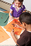 Education preschool art activity 3 year olds boy and girl drawing with markers drawing on same piece of paper vertical handedness girl using right hand boy using left hand