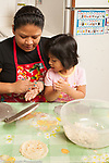 3 year old girl with mother in kitchen at home making tortillas, watching her and learning how to make them